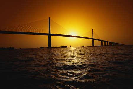 tampa bay: This is the Sunshine Bridge. It is one of the longest suspension bridges in North America. The ocean is shown in the foreground with the bridge in the distance.