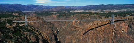 extensive: This is the Royal Gorge Bridge which is the worlds highest suspension bridge. It is 1053 Ft. above the Arkansas River. Mountains are in the background with red rock below the bridge.