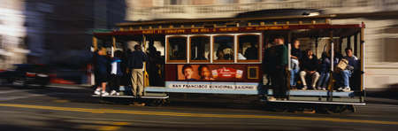 This is a Cable Car riding from Nob Hill. There are passengers holding on to the poles, standing and also sitting down in the car. It is slightly blurred as it is moving down the road.