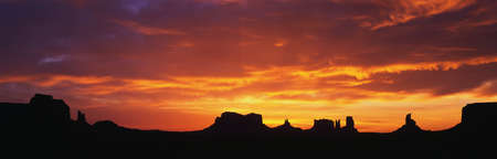 This is sunrise on Monument Valley. The rocks are in silhouette against an orange sky.