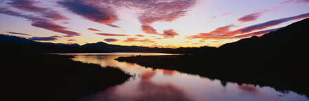extensive: This is Lake Casitas at sunrise. There is a pinkish glow from the sun reflected in the lake. Stock Photo