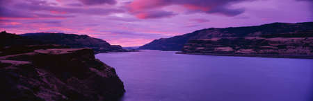 This is east of Portland. It shows sunrise from Washington State which is on the left looking at Oregon on the right. The river winds toward the back of the image showing the banks on either side. The sky has a pink and blue glow from the sunrise.