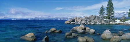 This is Lake Tahoe after a winter snow storm. There is a full moon over the lake and snow on the sandy shore. photo