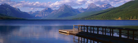 mcdonald: This is a boat dock at Lake McDonald. The blue water of the lake surrounds the dock with mountains in the background.