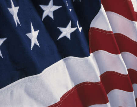 american history: This is an American flag with waves folding over the blue field of stars and red and white stripes.