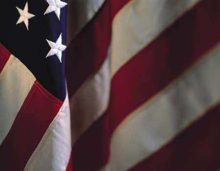 american flags: Esta es una bandera americana colgando. Existen tres estrellas en la esquina superior izquierda, con las rayas de descender en un pliegue diagonal cruzando hacia la esquina inferior izquierda. El resto de las franjas se desvanecen en el fondo en un Directivas horizontal