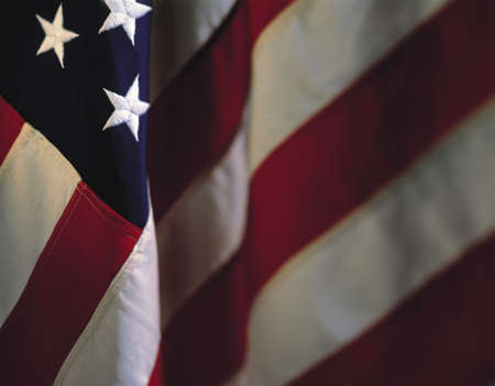 american history: This is a hanging American flag. There are three stars in the upper left hand corner, with the stripes dropping down in a fold crossing diagonally toward the bottom left hand corner. The rest of the stripes fade into the background in a horizontal directi Stock Photo
