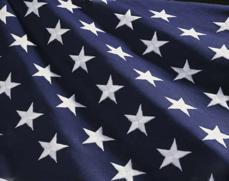american history: These are the stars of the American flag. They are against their blue field, climbing upward toward the corner of the image as if they were situated on small stairs that move up in levels..