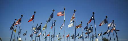 flagpoles: There are 50 State Flags waving in the wind on flagpoles equal distant apart against a blue sky, with the American flag in the center. These are located at Sea World. Stock Photo