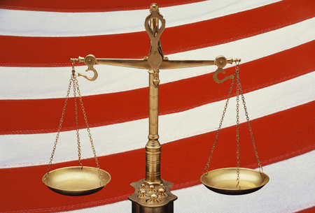 These are the golden Scales of Justice set against a background of the red and white stripes of the American flag. The scales are in a balanced position. This is a digitally created image.