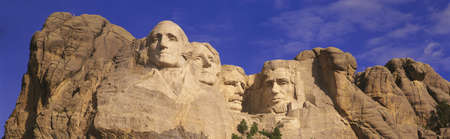 george washington: This is a close up view of Mount Rushmore National Monument against a blue sky. It shows the four faces of George Washington, Thomas Jefferson, Theodore Roosevelt, and Abraham Lincoln. Editorial