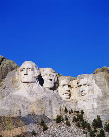 This is a vertical image of Mount Rushmore National Monument showing the four faces of George Washington, Thomas Jefferson, Theodore Roosevelt, and Abraham Lincoln. Editorial