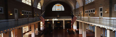 great hall: This is the interior of the Great Hall at Ellis Island which signifies immigration to the United States.  There are two American flags flying posted at the center of the walls. Editorial
