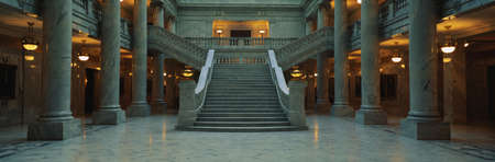 second floor: This is the interior of the State Capitol of Utah. Marble Columns are at the sides of a very wide, grand staircase leading to the second floor.