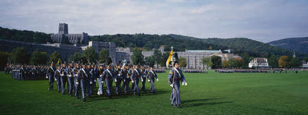 This is the exterior of the West Point Military Academy. Marching are the Homecoming Parade of Cadets in grey uniforms and tall hats, holding long guns. Stock Photo - 20515097