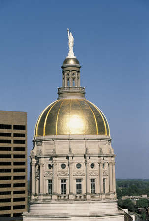 This is the dome of the State Capitol building. It is gold in color. There is a tall building to its left.