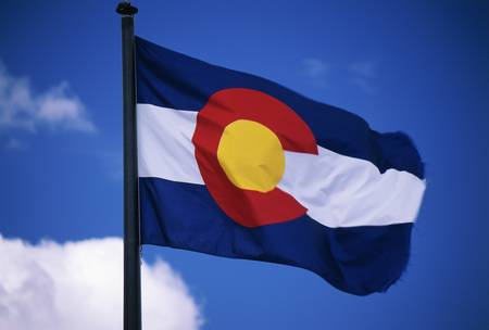 capital of colorado: This is the Colorado State Flag, waving in the wind situated on a flag pole. It is set against a blue sky. At the center of the flag is a large capital C.