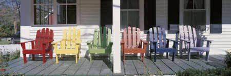 This is the Salt Ash Inn Bed and Breakfast. it is a large white house with a large front porch. This is a close up of the front porch with brightly colored wooden chairs in front of the windows.  Stock Photo - 20474727