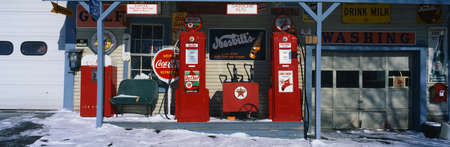 This is a vintage gas station with old style pumps that are red. It is a piece of Americana. It shows winter in New England. There is an old-fashioned Coke sign with other vintage signs. There is snow on the ground with a small bench and a garage door at