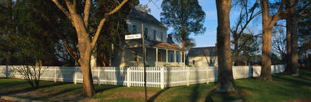 This is a photo of a typical suburban house on Main Street, USA. There is a white picket fence on a shaded, tree lined street with a green lawn. At the corner is a street sign that says, Main Street & Front Street. This is the Bonner House which was built Stock Photo - 20486442