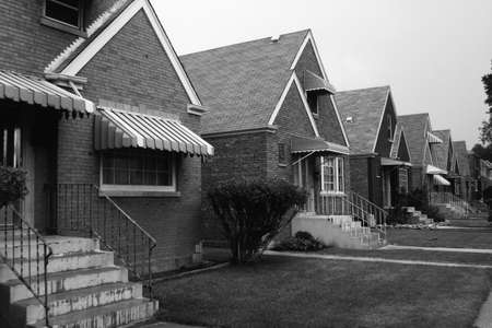 awnings: This is a black and white image of a row of single family houses. They are located on the south side of Chicago. They are brick houses with striped awnings over the front window and front door. There are steps and a thin railing leading up to the front do