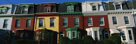These are typical urban style row houses. They are all lined up next to each other with neatly trimmed bushes in front of them. They are colorfully painted in red, white or yellow paint. They all have a single window on the top floor with two windows on t