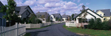 suburban street: This is a typical suburban American neighborhood. There are single family homes with a white picket fences in front of each house. A road leads down the center of the image that takes you past each house. There are trees beside each house.