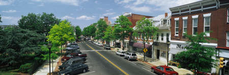 small town: This is the Eastern Shore of Maryland. It typifies small town America or Main Street USA. We see shop fronts on a tree lined street. There are cars parked in front of the shops on either side of the street. Editorial
