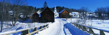 This is a small town in New England showing a white Methodist Church with steeple. There is a snow covered bridge in the foreground with older looking brown wood buildings behind it. The bare trees of winter surround the buildings. Stock Photo - 20486429