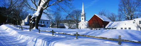 This town was settled in 1776. It is a typical image of New England in the winter. There is a white church with tall steeple, snow covered trees, a wooden fence in the foreground behind a snow covered road. There is also a red barn or building next to the Stock Photo - 20486422