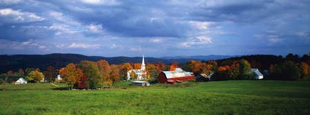 This is a view of the village in autumn. There is a typical New England white church with a tall steeple and a red barn. Stock Photo - 20486406