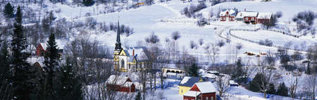 This is an aerial view of East Orange. There is a black steepled church and a small village. The village is covered in snow with houses spread across the field. Stock Photo - 20486435