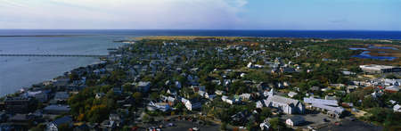 cape cod home: This is an aerial view of Cape Cod. We see the ocean on the left hand side and the new England town of Provincetown on the right.