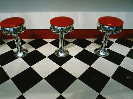 This is an art deco style restaurant. It has a black and white checkerboard tile floor with red vinyl stools next to the counter. It is a typical 50's style diner.