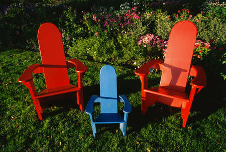 family unit: These are colored wooden lawn chairs. There are two large red chairs and one small blue chair in between the two large ones. They suggest a family unit. They are in a garden setting.