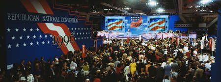 public spirit: This is the 1996 Republican National Convention that took place at the San Diego Convention Center. Senator Bob Dole and Jack Kemp were seeking the nomination. The view is overlooking the convention. There is a large crowd of people at the event.