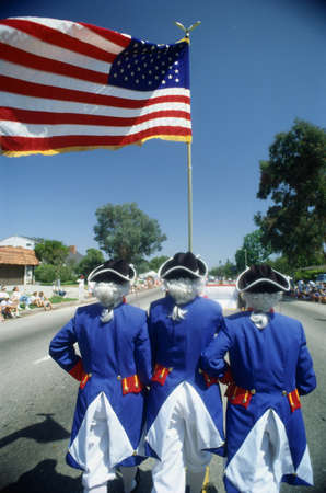This is an Independence Day Parade with men dressed as Revolutionary War soldiers holding the American flag. It demonstrates patriotism. Stock Photo