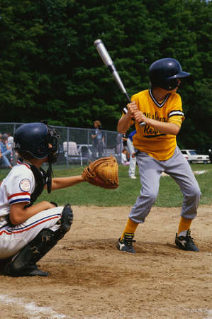 These are kids playing in a little league baseball game. It shows kids playing sports. There is a young boy up at bat with the catcher situated behind him.