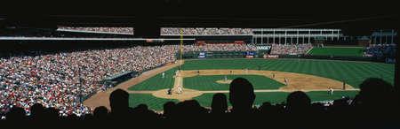 ballpark: Este es un gran juego de b�isbol de la liga se juega en el estadio. Los equipos son los Rangers de Texas vs Baltimore Orioles. Hay una gran multitud en las gradas y en primer plano son fans sentados en silueta. Editorial