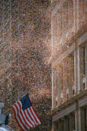 public spirit: This is a shot of confetti and ticker tape falling like snow at the Ticker Tape Parade for the Desert Storm Victory. An American flag is waving at the bottom left hand corner. Stock Photo