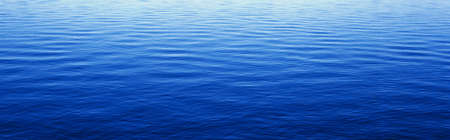 extensive: These are water reflections in Lake Tahoe. The water is a deep blue and the small ripples in the water form a pattern.