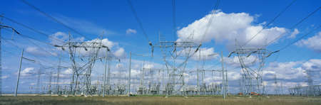 These are electrical utility lines set against a blue sky with white puffy clouds.
