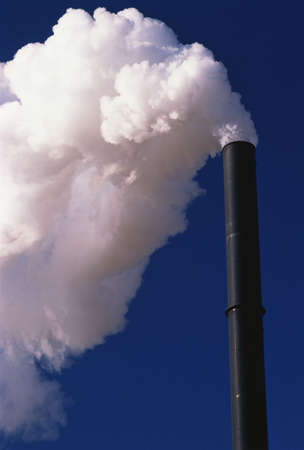 smokestacks: This is a Denver utility company. It is contributing to air pollution with its smokestacks. This shows one tall, black smokestack with billowing smoke coming out the top.