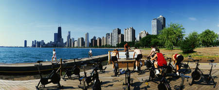 signifies: This is a spinning class taking place on North Avenue Beach at Lake Michigan. Several people are riding stationary bicycles with an instructor facing them in front. It signifies fitness. The Chicago skyline is in the background and it is a summer morning.