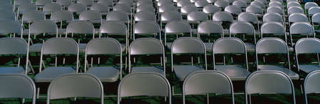 These are empty, grey folding chairs awaiting the crowd to attend the U.S. Naval Academy, Graduation Ceremony. They are neatly set up in rows side by side. Stok Fotoğraf