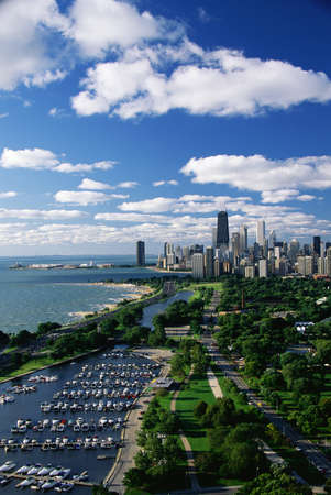 This shows Lincoln Park, Diversey Harbor, and Lake Michigan looking south toward the skyline. It has morning light in summertime. There are boats moored in the harbor next to the lake. photo