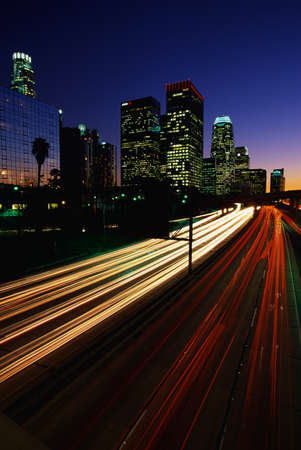 This is the Harbor Freeway with the streaked lights from rush hour traffic at sunset. The skyline is to the left of the freeway.
