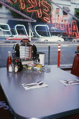 jukebox: This is the interior of a vintage Americana type diner. this is one of the tables inside the diner. It has the juke box selection at the table with diner fashion salt and pepper shakers, napkin dispenser and utensils set in front of a window. Editorial