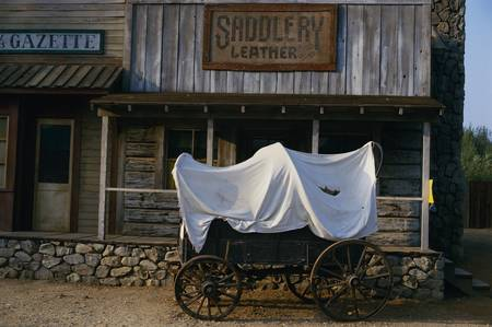covered wagon: This is the Paramount Ranch showing what the old west looked like. There is a covered wagon in front of an old newspaper office.