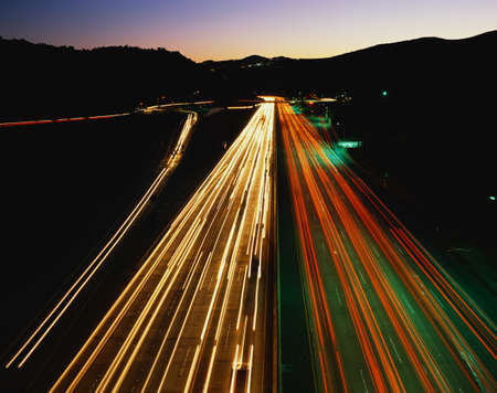 briskness: This is the San Diego Freeway also known as the 405. These are the streaked lights of the cars at night at rush hour. Stock Photo